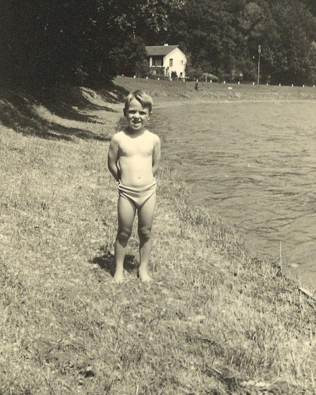 Schwarz-Weiss-Fotografie mit einem kleinen Bub, der in Badehosen am Ufer eines Flusses steht.