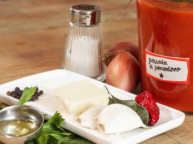 auf einem Teller liegen die Zutaten für einen Tomatensugo bereit: Butter, Zwiebeln, Salz und Pfeffer, Lorbeer, Tomatenpüree, Pelati.