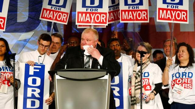 Rob Ford steht mit einem Taschentuch vor dem Mund am Rednerpult einer Wahlkampfveranstaltung.