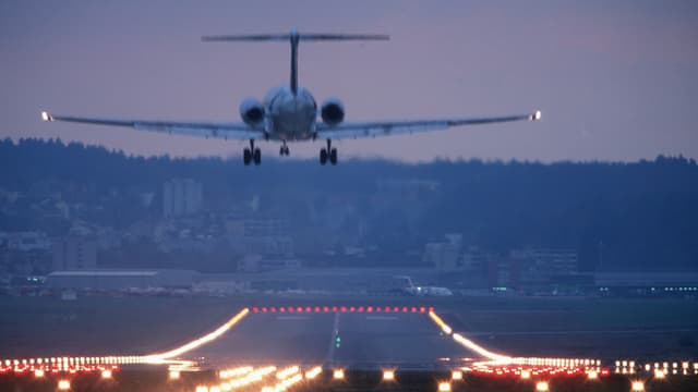 Ein Flugzeug landet auf einer beleuchteten Piste.