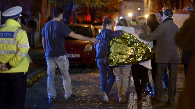 Junge Menschen auf einer nächtlichen Strasse, eine junge Frau ist in eine Foliendecke gehüllt.