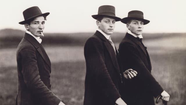 Drei Männer auf einem Foto. Sie tragen alle Hut und halten einen Stock.