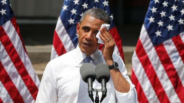 Barack Obama wischt sich den Schweiss mit einem weissen Taschentuch von der Stirn, vor ihm Mikrofone, hinter ihm US-Flaggen.
