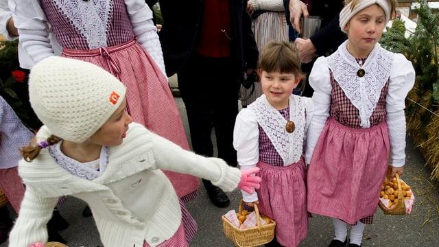 Drei Mädchen mit traditionellen rosa Kleidern und Körben.