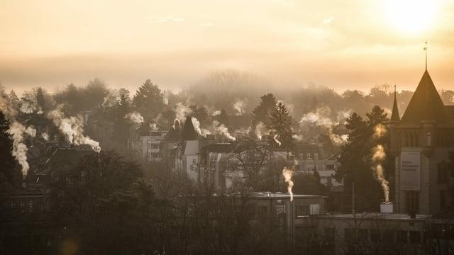 Winterlich-morendlicher Blick über Bern, die Heizungsschlote der Häuser rauchen.