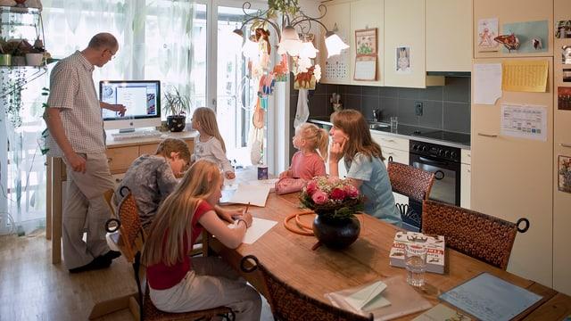 Familie lernt mit Kindern in Küche.