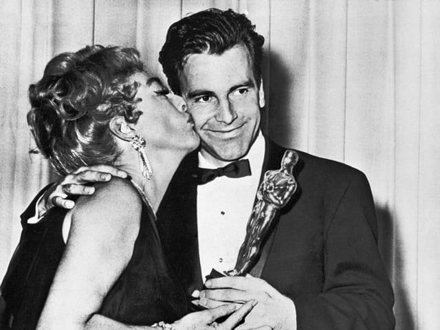 Schauspielerin Joan Crawford küsst den lächelnden Maximilian Schell mit der Oscar-Statue in der Hand.