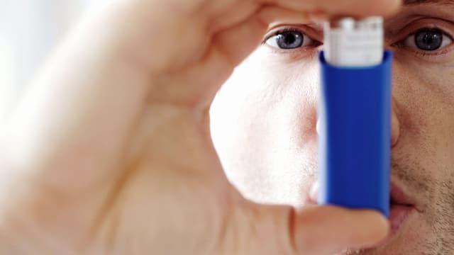 Mann hält sich einen Asthma-Inhalator in den Mund