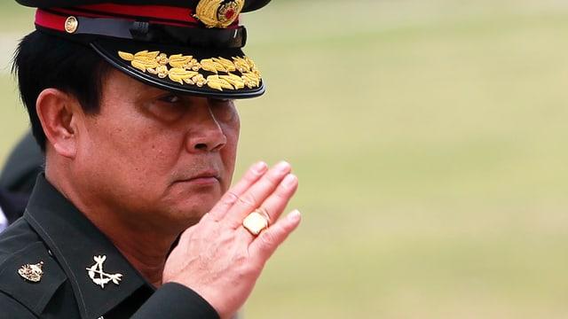 Prayudh in Militäruniform, grüsst mit der Hand am Hut.