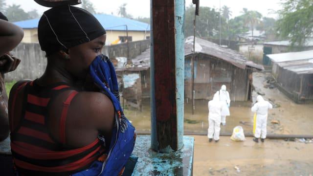 Frau auf einem Balkon. Im Hinergrund auf der Strasse Hilfspersonal in Schutzkleidung
