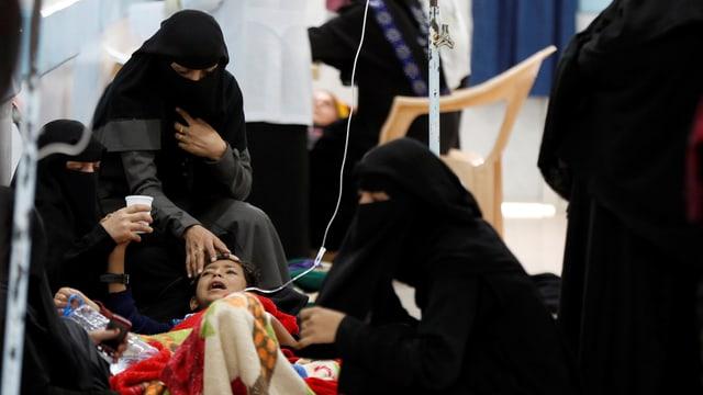 Frauen in Burka pflegen ein schreiendes Kind