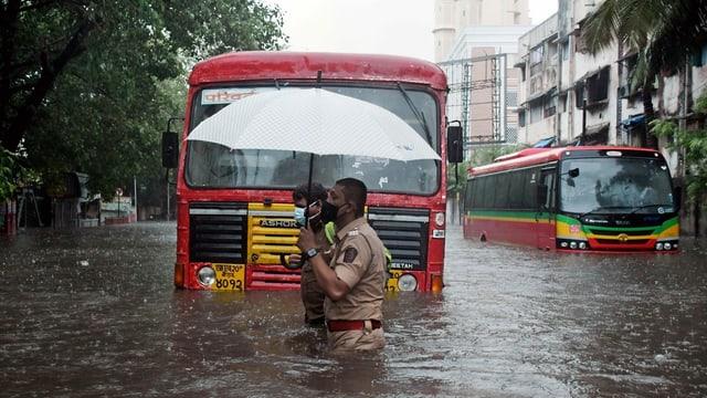 Ein indischer Polizit hilft einem Busfahrer die überschwemmte Starsse zu überqueren.