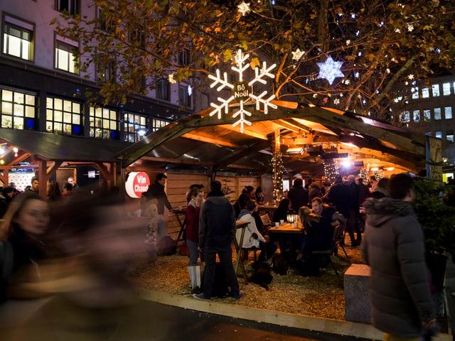 Menschen sitzen vor einem Häuschen auf dem Lausanner Weihnachtsmarkt