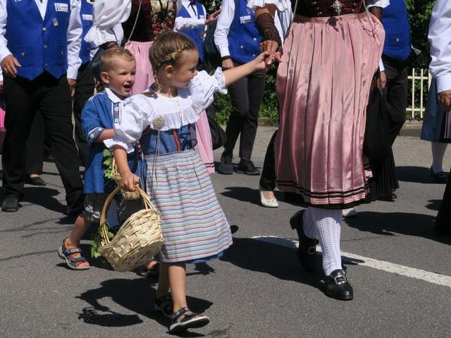 Zwei Kinder - das Mädchen an der Hand einer Frau