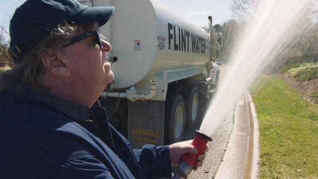 Michael Moore giesst mit Wasser aus Flint einen Garten.