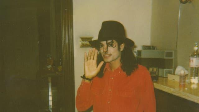 Michael Jackson in rotem Hemd und schwarzem Hut. Er winkt in einem grobkörnigem Foto dem Betrachter entgegen.
