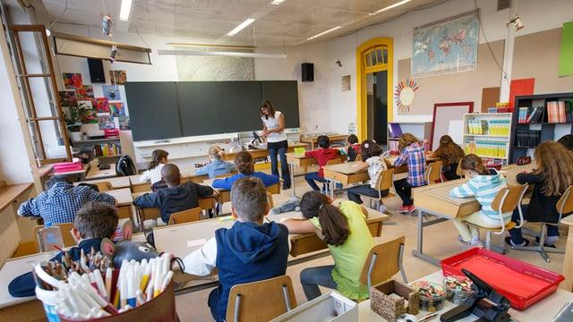 Blick in ein Klassenzimmer mit arbeitenden Schüler und Schülerinnen und der Lehrerin