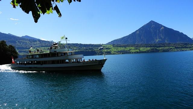 Ausflugsschiff auf dem Thunersee, im Hintergrund der Niesen vor einem wolkenlosen Himmel.