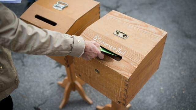 Ein Mann wirft einen Stimmzettel in die Urne.