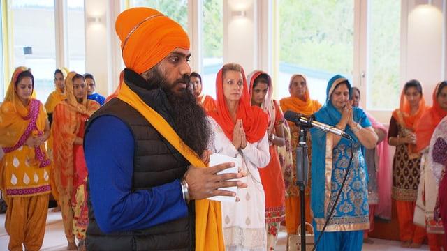 Sikh mit Turban im Vordergrund, dahinter betende Frauen.