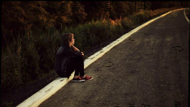 Eine junge Frau sitzt allein und verlassen auf den Randsteinen einer Strasse.