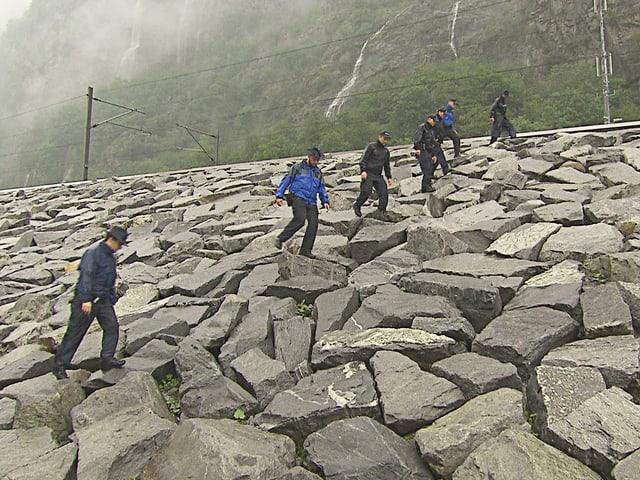 Einige Sicherheitsmitarbeitende überqueren ein Feld voller Steine.