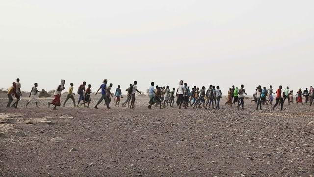 Menschen gehen über ein karges Steinfeld in einer langen Reihe, sie flüchten.