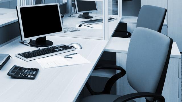 Bürosessel mit Computer auf Tischen
