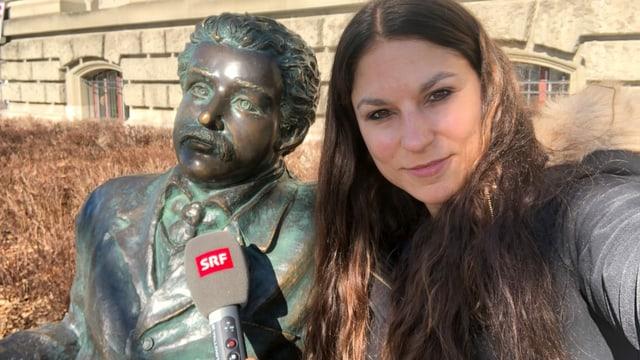 Selfie von Reporterin mit einer Albert Einstein Statue, die auf einer Bank sitzt