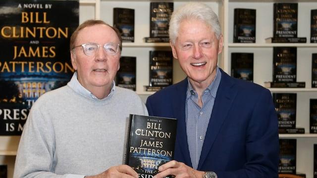 James Patterson und Bill Clinton halten ihren Krimi in die Kamera.