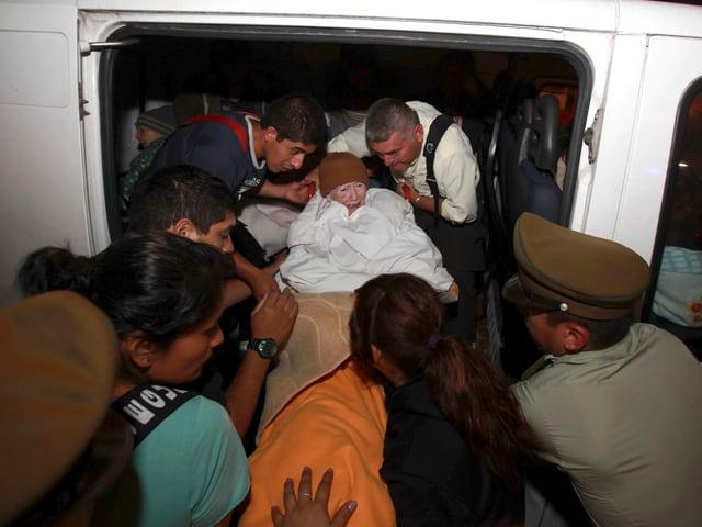 Polizei und Helfer tragen eine alte Frau aus einem Auto.