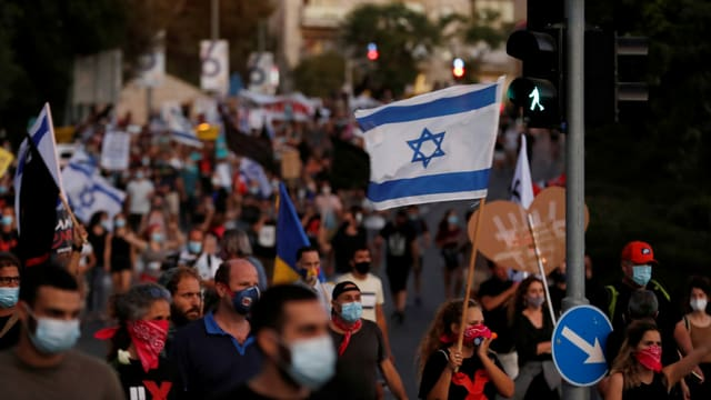 Protestierende tragen Schutzmasken und halten Israels Landesflagge.
