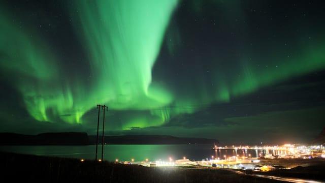 Grünes Polarlicht über einer Stadt