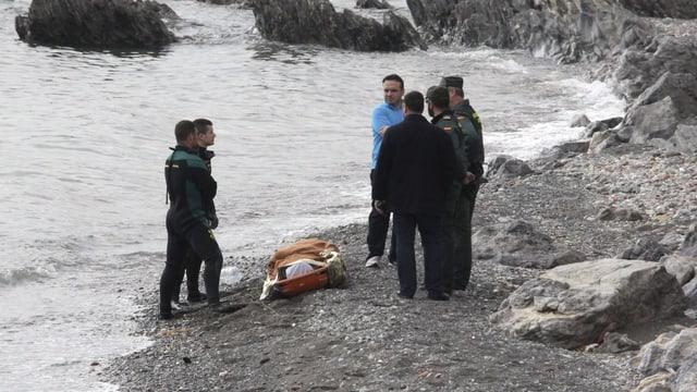 Polizisten und Taucher stehen an der Küste neben der Leiche eines Flüchtlings.