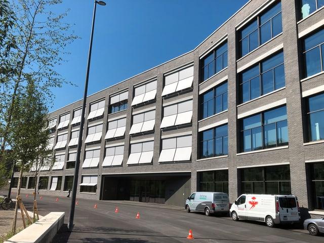 Ein grosses, modernes und graues Bürogebäude mit grossen Fenstern.