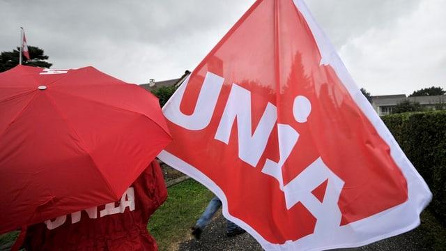 Ein Unia-Gewerkschafter mit Schirm und Fahne.