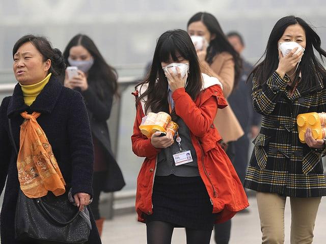 Frauen, die sich eine Maske vor ihr Gesicht halten.