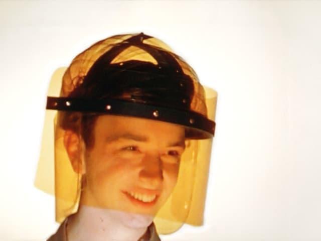 Ein Mann trägt einen Helm, der mit orangefarbener Folie umwickelt ist.