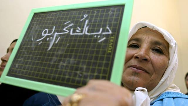 Eine Frau mit Kopftuch hält eine Kreidetafel mit arabischer Schrift in die Kamera.