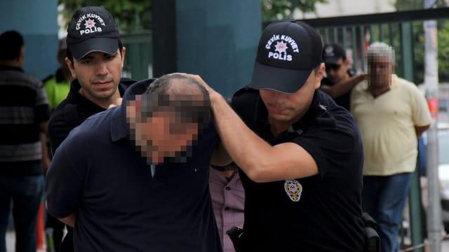 Zwei Polizisten führen einen Soldaten in Zivil mit gesenktem Kopf ab.