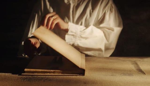 Jemand mit einem alten Leinenhemd und Siegelring öffnet ein altes Buch