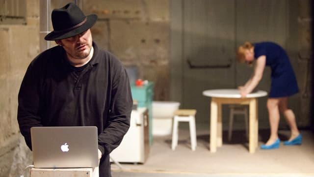 Ein Mann mit Hut und dunklem Pullover steht an einem aufgeklappten Laptop.