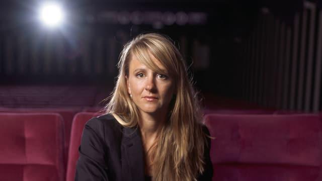 Seraina Rohrer in einem roten Kinosessel.