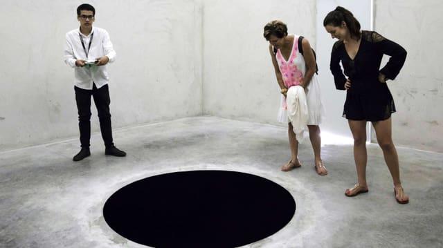 Im Museum: Drei Leute schauen auf ein schwarzes Loch im Boden.