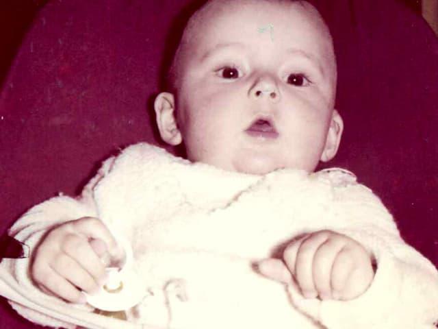 Kleines Baby auf rotem Kissen.