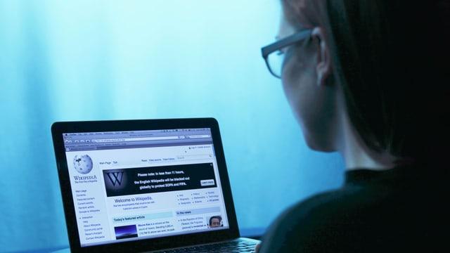 Ein Frau sitzt im Dunkeln vor einem Laptop.