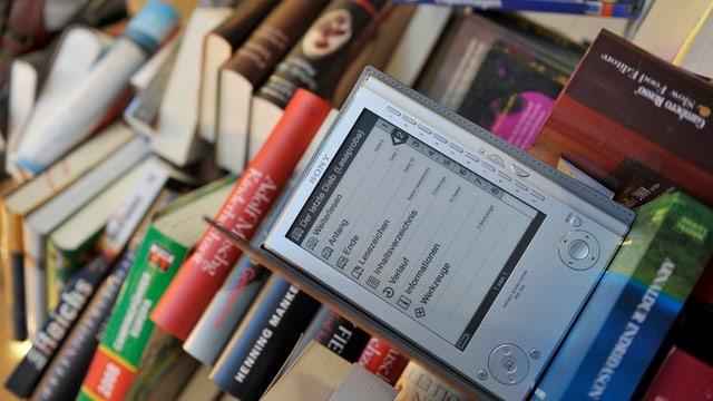 Ein E-Book-Reader liegt auf einem Bücherstapel.