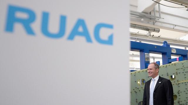 Urs Breitmeier rechts neben einem Schild mit blauem Schriftzug «RUAG»