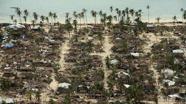 Luftaufnahme eines zerstörten Dorfs am Meer.