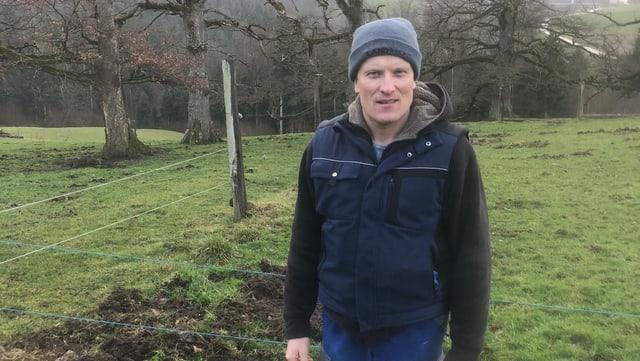 Dominic Sprunger vor einer vor Wildschweinen verwüsteten Wiese.